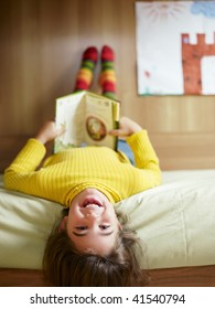 girl lying on bed and reading book