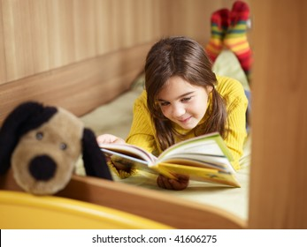 girl lying on bed and reading book. Copy space