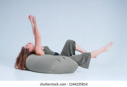 The girl is lying on a chair bag in the studio, on a white background in a green dress