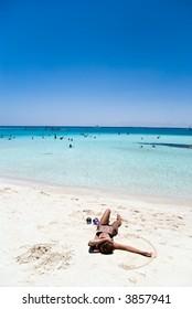 girl lying on coral beach