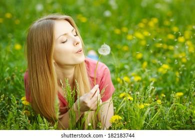 Girl lying on the field of dandelions blowing dandelion, wish concept