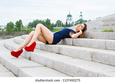 girl is lying on the granite steps of the stairs