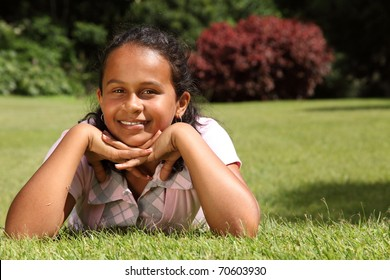 Girl lying on grass chin on hands smiling