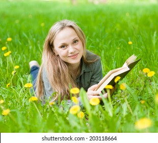 girl lying on grass with dandelions reading a book and looking at camera