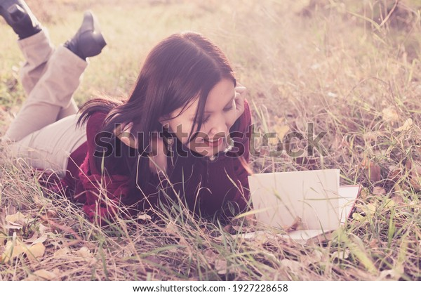 Girl lying on grass in sunset light with a book. Spring or summer warm weather relax concept.