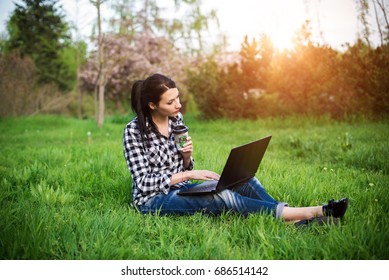 girl lying on the grass and using laptop and typing with coffee.