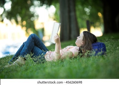 Girl lying on green grass outdoors in summer or spring reading a white book wearing jeans