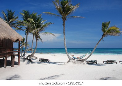 Girl lying on a hammock on a Caribbean beach