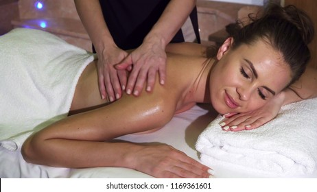The girl is lying on a massage table. Her body shines with butter. Another girl does her a good massage. The girl looks very pleased and relaxed