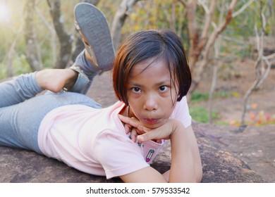 Girl lying on a rock  make gusture