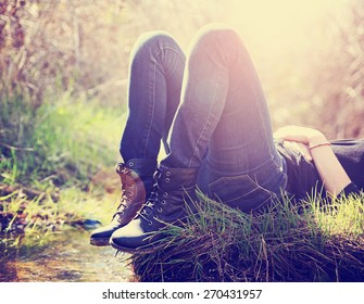 a girl lying on a small island in a stream with jeans and black combat boots on backlit with the setting sun toned with a retro vintage instagram filter effect app or action