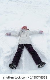 Girl lying on the snow with arms outstretched to the sides