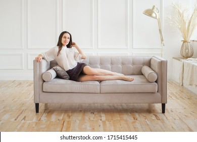 The girl is lying on the sofa in a bright Studio