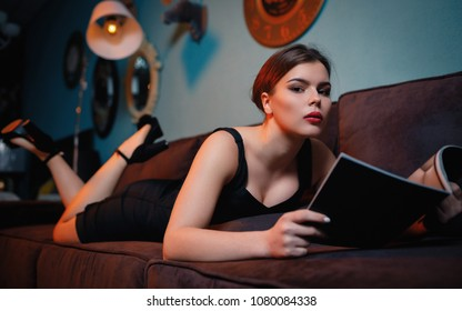 Girl lying on sofa and reading magazine. Attractive woman relaxing at home, looking for latest fashion trends, celebrities lives, reviewing show business news, examining goods catalogue at free time