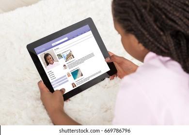 Girl Lying On White Carpet Surfing On Social Site Using Digital Tablet