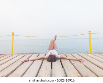 Girl lying on a wooden mole / pier and enjoying the ocean.