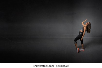 girl made sport with smile on face, dark background
