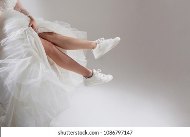 The girl in a magnificent wedding dress and white sneakers, legs close-up. Runaway bride, free space on the right