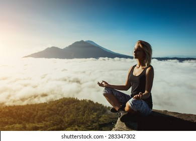 Girl make meditation above the clouds with peak of volcano on background