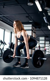 The girl makes the dead lift in gym with barbell