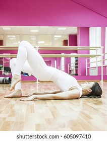 Girl makes exercises and does yoga in pink dance class