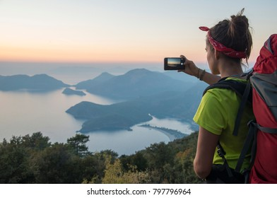 Girl makes landscape photo with help of smartphone. Landscape contains sundown over sea and mountains. Travel scene, so woman has backpack.