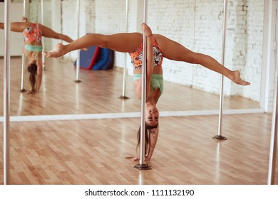 Girl makes a leg split on a pole in the studio