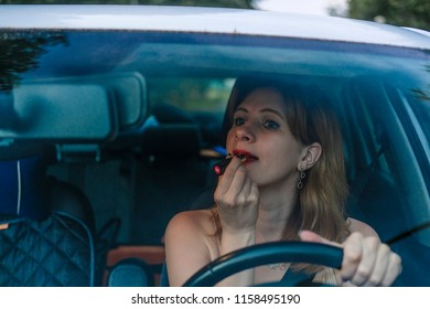 Girl makes up lips in a car