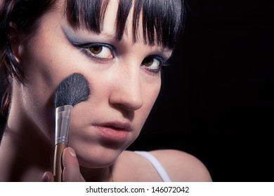Girl makes makeup. Isolated on white background