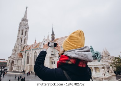 A girl makes a photo on the phone. The girl in the yellow winter hat takes off. I love Budapest. Parliament building in Budapest. Travel to Hungary. Travel to Budapest. photo architecture.
