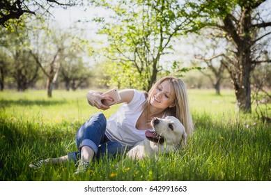 The girl makes selfie with a labrador