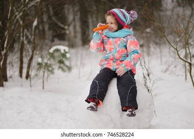 girl makes snowman in winter park