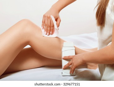 girl makes a waxing on his feet to the client, silky skin in women