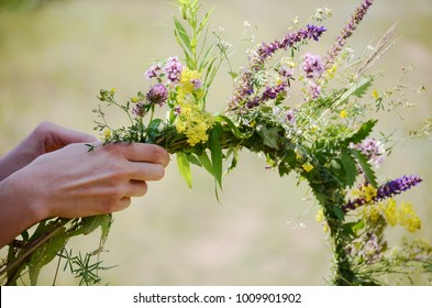 The girl makes a wreath at the head. The process of weaving a wreath with herbs and wild flowers. Summer. Spring
