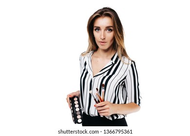 girl makeup artist on a white background holding a small eye shadow brushes and a palette
