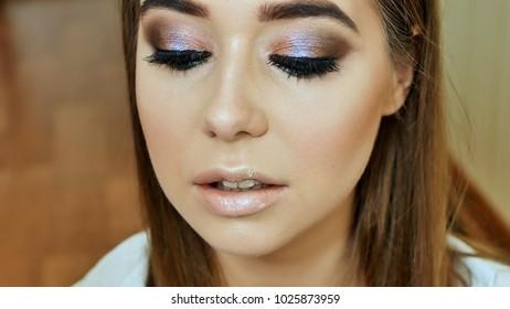 Girl makeup artist paints girl's lips model in gentle pink color