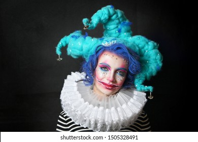 girl in makeup and costume jester . clown girl with bright makeup in blue wig On black background. She looks at the camera .