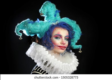 girl in makeup and costume jester . clown girl with bright makeup in blue wig On black background. She looks naughtily at the camera