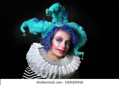 girl in makeup and costume jester . clown girl with bright makeup in blue wig On black background