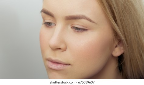 Girl with makeup foundation on adorable face. Cute woman with healthy young skin and long blond hair on grey background. Visage, cosmetics, skincare and make up. Beauty salon - Shutterstock ID 675039637