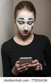 The girl with makeup of the mime holding the smartphone