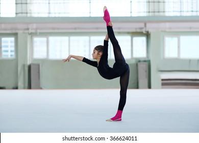 girl making a balance in training rhythmic gymnastics