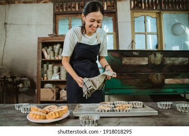 girl making the cake in an apron using cloth chose a hot freshly baked cake pan in the kitchen as a background