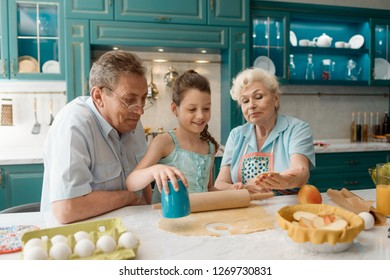Girl making cookies with grandparents. Granny and granddad teaching granddaughter how to make simple pastries.
