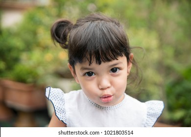 girl making a cute pucker face and little Asian girl with sassy expression