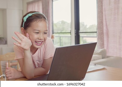Girl making facetime video calling with laptop at home, using zoom  online virtual class , social distancing,homeschooling,learning remotely during covid coronavirus pandemic, new normal concept