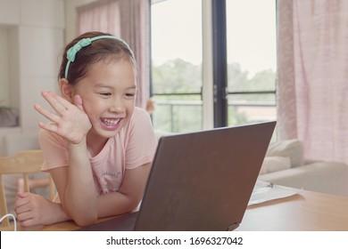 Mixed Rasse junge asiatische Mädchen, die zu Hause Videoanrufe mit Laptop anbieten, mit Zoom-Online-App, sozialer Distanzierung, Isolation, Schulunterricht, Fernstudium