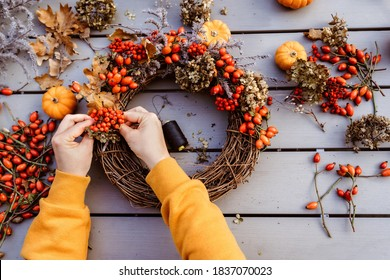 Girl making floral autumn door wreath using colorful rosehip berries, rowan, dry flowers and pumpkins. Fall flower decoration workshop, florist at work.