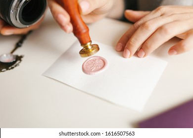 Girl making greeting card and sealing the envelope with wax sealing stamp