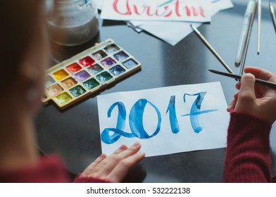 girl making greetings cards. Hand lettering. Happy new year 2017 and Merry Christmas. writting 2017 with watercolor on paper. Close up on hands